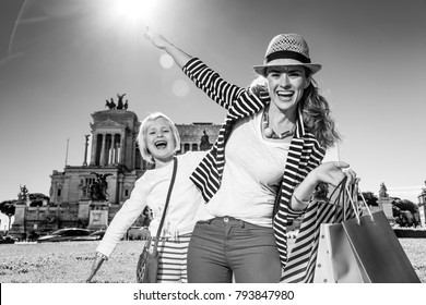 Roman Holiday. smiling stylish mother and daughter tourists in the front of Palazzo Venezia in Rome, Italy with shopping bags having fun time