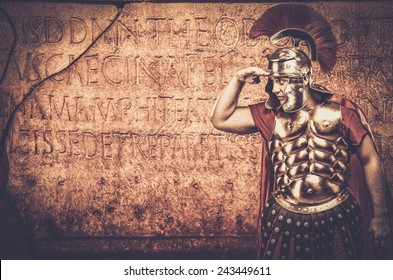 Roman legionary soldier in front of  wall with ancient writing
