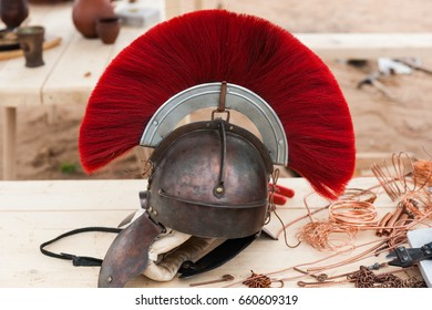 Roman military helmet made of copper with a centurion crest on top. Copper wires and tools on a wooden table.