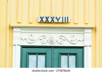 Roman number 39 XXXVIII (should have been XXXIX if correct) over a green door on a yellow and white building.