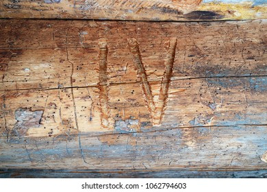 Roman numeral 4 cut on a log, wooden texture on a log house