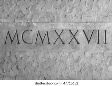 Roman numerals engraved in textured stone on outer wall of an historic Courthouse building in Santa Barbara, California.