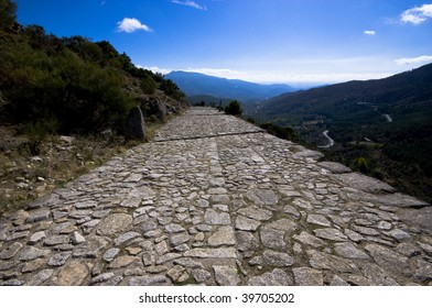 A Roman road crossing the Gredos mountains of Spain heading upwards towards the distant blue horizon.  Concept of a road to nowhere, or towards the future.