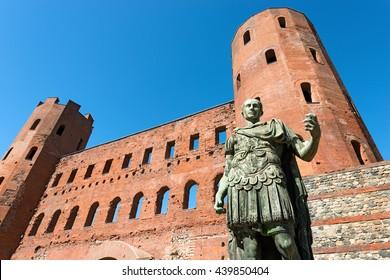 Roman statue of Julius Caesar and ancient ruins of Palatine Towers in Torino (Porta Palatina), Piemonte, Italy
