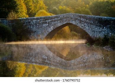 Roman stone bridge, with reflection in the water and sun rays entering from below and with fog, mist