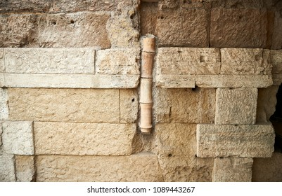Roman stone wall with rest of pipe