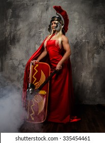 Roman warrior woman in red fluttering dress holds sword and shield.