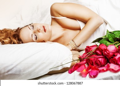 Romance. Beautiful sleeping woman in white bed with red roses