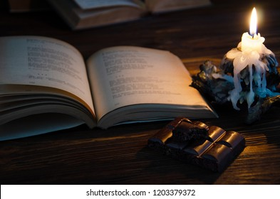 Romance. Book of poems, black porous chocolate and a candle on a brown wooden background.