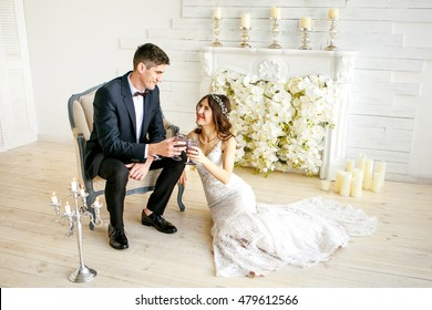 Romance bride and groom. The bride sits on a chair, the bride on the floor near the fireplace. They were holding glasses of wine.