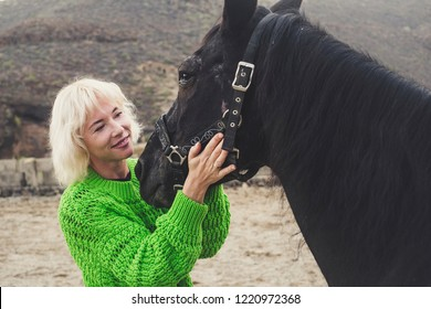 Romance concept image with blonde attractive lonely woman with darj horse in toudoor leisure activity together. Love between humans and animals