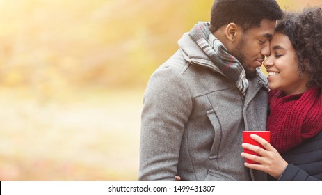 Romance and fall mood. Couple in love with coffee cup, dating in park at autumn