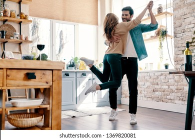 Romance. Full length of beautiful young couple in casual clothing dancing and smiling while standing in the kitchen at home
