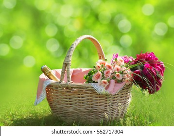 Romance, love, valentine's day concept - wicker basket with bouquet of flowers, bottle wine on the grass. Spring fresh sunny background