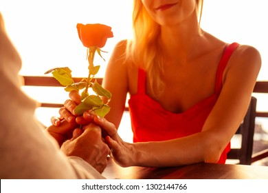 romance marriage proposal by the sea tropical paradise beach beachfront restaurant.a man in a white shirt and a beautiful blonde in red dress sitting summer cafe,rose Happy Valentine's Day February 14