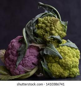 romanesco green and purple cauliflowers blurred background