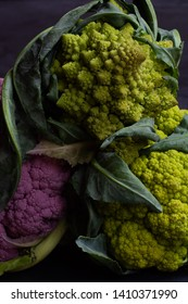 romanesco sitting on top of purple and green cauliflowers vertic