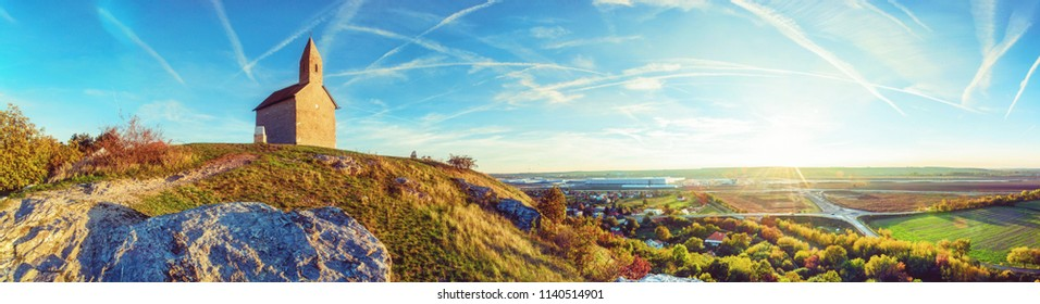 Romanesque church Saint Michael, Drazovce village and industrial park Nitra in sunset, Slovak republic. Autumn panoramic scene. Landscape in middle Europe. Vivid photo filter.