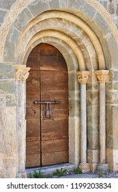 Romanesque entrance arch and capital with antique wooden door. Spain