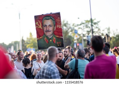 Romania, Bucharest - August 10, 2018: Protesters displaying an illustration of Liviu Dragnea as communist during violent protest in Victoria Square