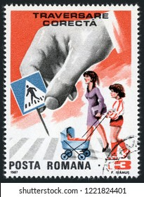 ROMANIA - CIRCA 1987: post stamp printed in Romania (Romana) shows woman and child with stroller crossing street; sign be aware of pedestrian crossings; traffic safety; Scott 3498 A996 3 l; circa 1987