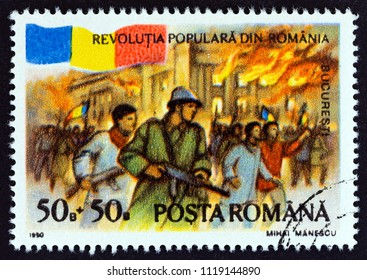 "ROMANIA - CIRCA 1990: A stamp printed in Romania from the ""Popular Uprising"" issue shows Republic Palace ablaze, Bucharest, circa 1990."