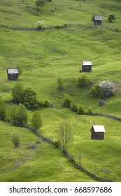 Romania, fenced in pastures dotted with small barns on a slope in the Carpathians near Sadova