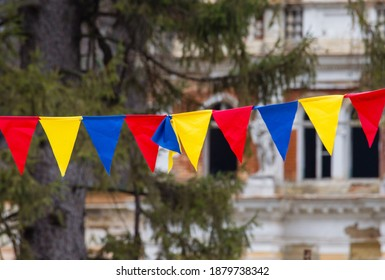 Romania flag garland in the city park for an anniversary moment.  Hanging bunting for Romanian National Day. Colorful garland with triangular flag of Romania. Red yellow and blue. Great Union Day