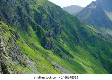 Romania, Romanian Carpathians - Fagaras Mountains, traverse Turnul Vartopul in a lush green and tourist trail with silhouette of tourists