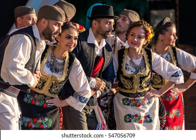 """ROMANIA, TIMISOARA - JULY 7, 2016: Young Serbian dancers in traditional costume, perform folk dance during """" International Festival of hearts """" , July 6, 2016 in Timisoara."""