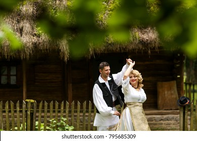 Romanian couple wearing traditional costume and posing in front of traditional old house