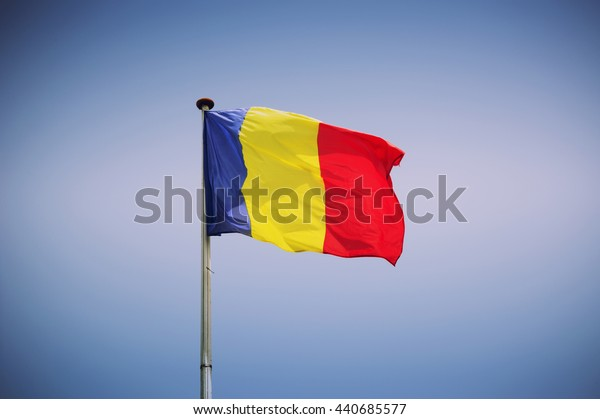 Romanian flag on the mast isolated on blue background