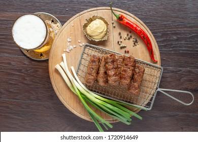 Romanian meatballs barbecue with mustard and beer (Mici cu mustar si bere la gratar)