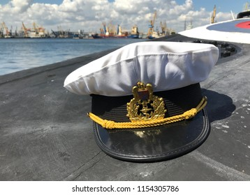 Romanian navy officer hat on submarine deck in a harbor.