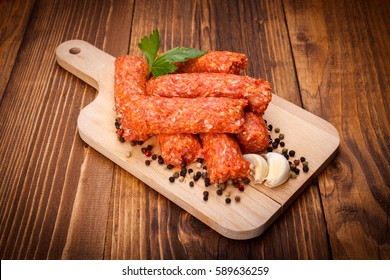 Romanian pork and lamb sausages, mititei on cutting board with pepper and garlic