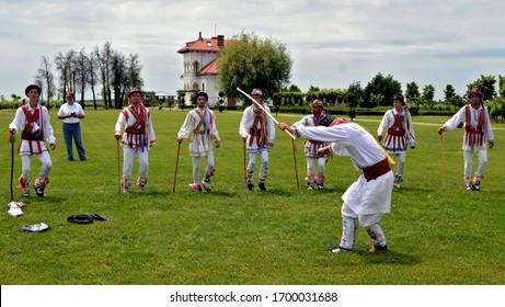 "Romanian rustic festivities of ""Calusari"", men dressed in colorful clothing dancing in a spring festival after Easter, Dragasani, Dolj / Romania - 5/28/2018"