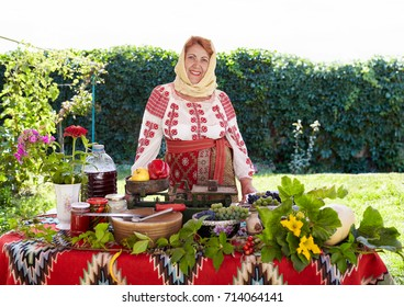 Romanian senior woman dressed in national costume, showing local agricultural products.
