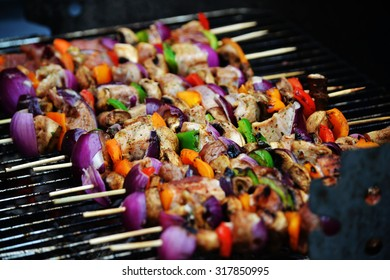 Romanian style charcoal grill. Chicken, mushrooms, peppers and onion on skewers.
