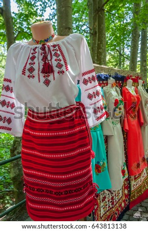 Romanian traditional costumes on mannequins and hangers shown outdoors.