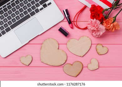 Romantic accessories for woman on pink wood. Flat lay, top view. Laptop, lipstic, flowers and heart shaped wooden hearts.