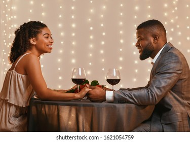 Romantic african american couple in love having date at restaurant, drinking red wine and holding hands, side view, empty space