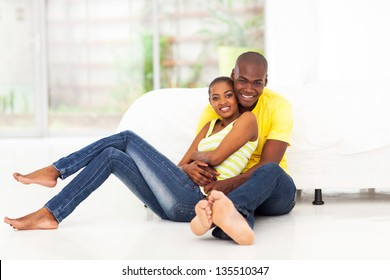 romantic african american couple sitting on bedroom floor