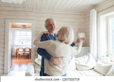 Romantic aged couple relaxing in country house dancing in living room, happy senior husband and wife sway in waltz looking in eyes, elderly man and woman have fun spending weekend at home together