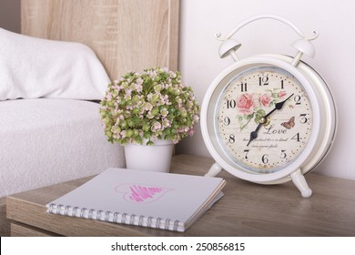 Romantic alarm clock, flower and love note on bedside table