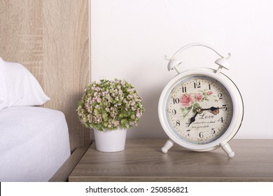 Romantic alarm clock and flowers on bedside table