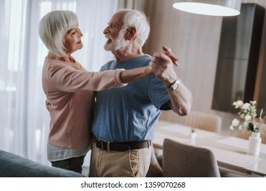 Romantic in any age. Waist up side on portrait of joyful elder husband and wife feeling love while dancing together at home - Shutterstock ID 1359070268