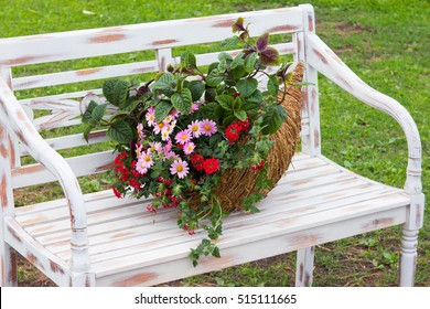 A romantic arrangement with a cornucopia filled with flowers on a park bench in the garden.