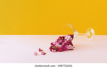 Romantic arrangment with martini glass and red and pink flowers spilled. Fun and bright arrangment. Wedding or engagement party concept.