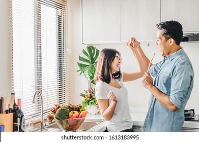 Romantisches asiatisches Ehepaar in Liebe tanzt und lächelt beim Kochen in der Küche zusammen