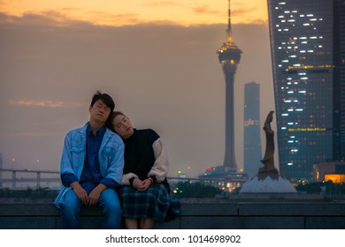 Romantic Asian couple sitting next to Kun Iam Statue and Macau Tower Convention. Woman sleeping on shoulder of man in Macau, China, Asia.